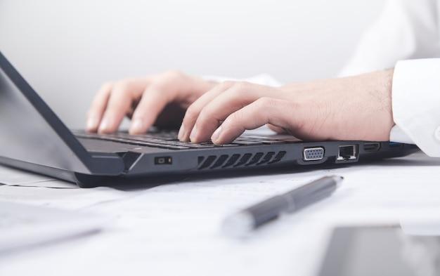 Бизнесмен, набрав на клавиатуре компьютера.