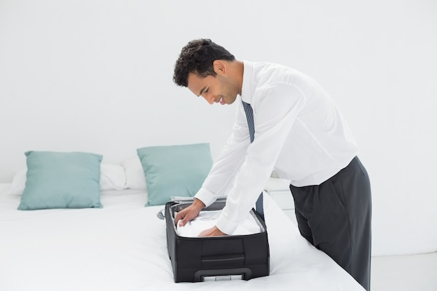Businessman unpacking luggage at hotel bedroom