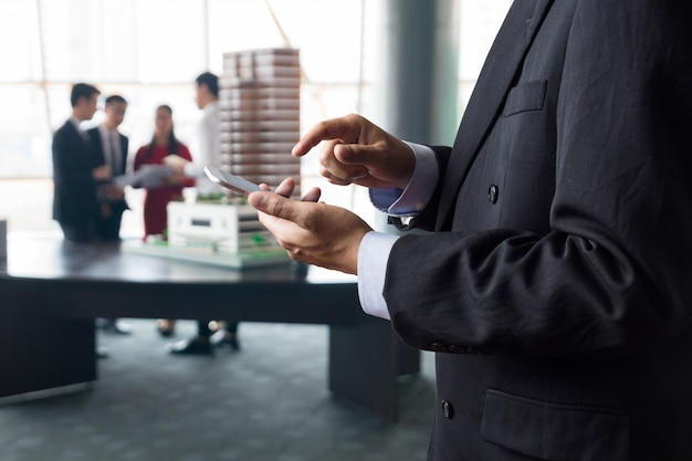 Businessman use digital wireless smartphone while meeting with client or colleague