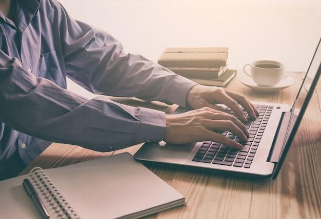 사업가 나무 사무실 테이블에 일상적인 작업에 대 한 노트북 및 스마트 폰 사용.