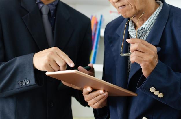 사업가는 비즈니스 커뮤니케이션이나 온라인 마케팅을 위해 휴대전화와 태블릿을 사용합니다.