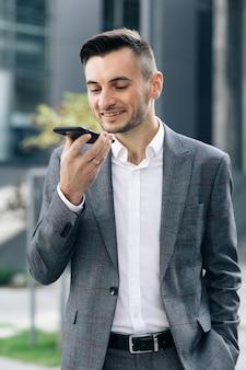 Бизнесмен использует смартфон для отправки голосовых сообщений на открытом воздухе в центре города