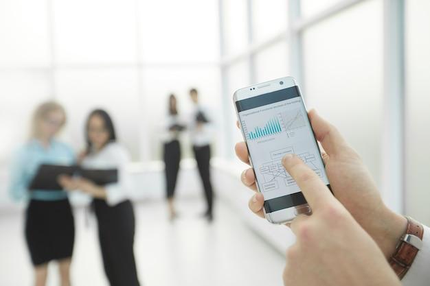 사업가 스마트 폰을 사용하여 재무 데이터를 확인합니다.