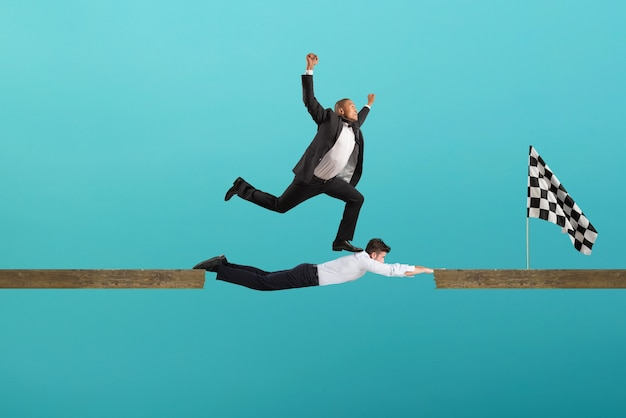 Businessman uses his body like a bridge to help his coullague to reach the flag. concept of teamwork and partnership. cyan background