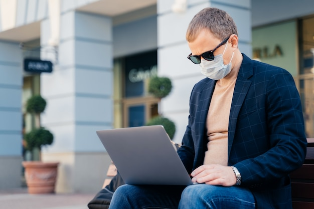 Businessman uses laptop computer for distance work, wears protective mask
