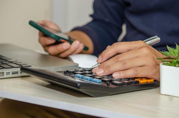 Бизнесмен с помощью калькулятора держит ручку и мобильный телефон на столе с ноутбуком, работающим из дома.