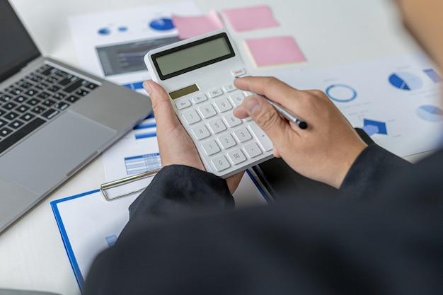 Бизнесмен, используя калькулятор для вычисления чисел в финансовых документах компании, анализирует финансовые данные за прошлые периоды, чтобы спланировать, как развивать компанию. финансовая концепция.
