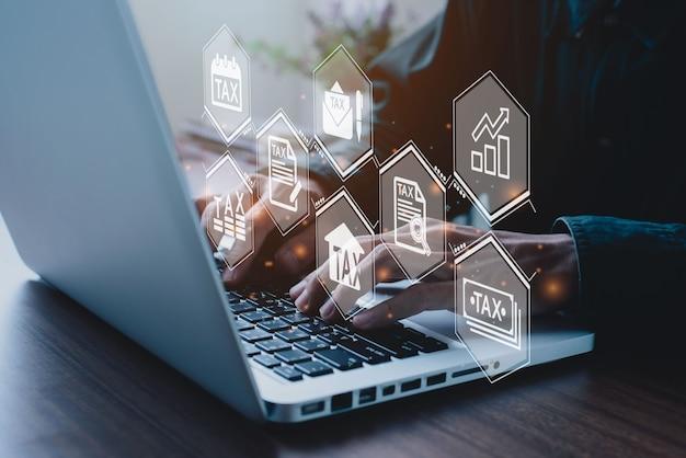 コンピューターを使用して、納税のためにオンラインで個人所得税申告書に記入するビジネスマン。税務、会計、統計および分析研究の概念