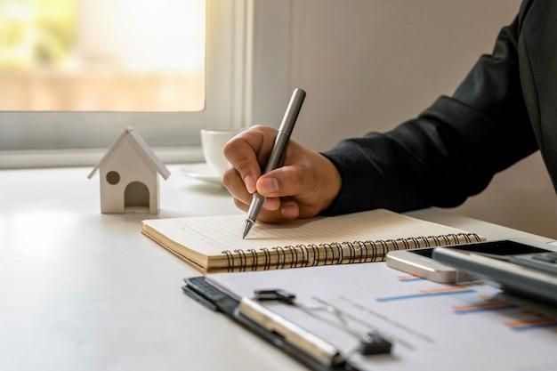 ペンを使用してデスクワークの財務報告を書き留めるビジネスマン