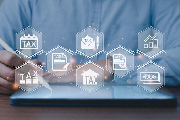 納税のためにオンラインで個人所得税申告書に記入するためにタプレットを使用しているビジネスマン。税務、会計、統計および分析研究の概念