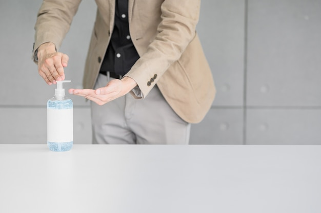 オフィスでコロナウイルスの拡散を防ぐために手を洗うアルコールゲルまたは抗菌せっけん消毒剤を使用しているビジネスマン
