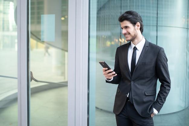 ビジネス環境で彼のスマートフォンでアプリを使用しているビジネスマン