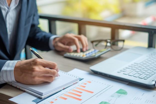 Businessman using calculator for analysis maketing plan