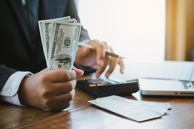 電卓を使用してお金を保持しているビジネスマンは、商業経費を計算します。
