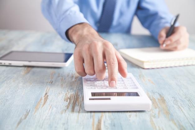電卓を使用してメモ帳に書くビジネスマン。