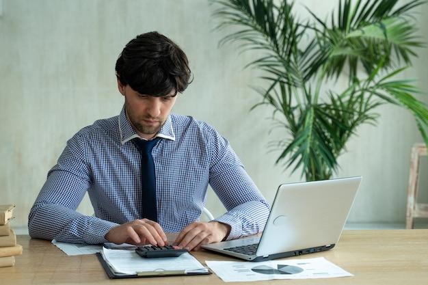 Бизнесмен, использующий калькулятор на офисном столе с технологией удаленной работы ноутбука и концепцией людей