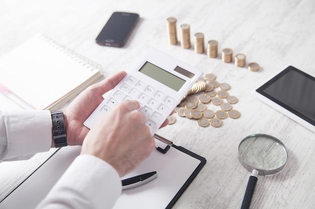 Бизнесмен с помощью калькулятора с монетами на столе.