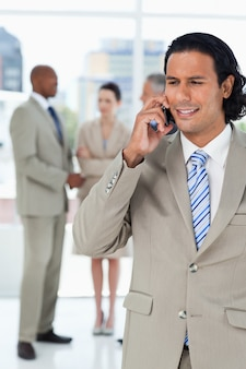 Businessman using a cell phone while his team is talking behind him