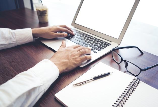 Бизнесмен, использующий компьютерный ноутбук с пустым экраном в кафе-магазине