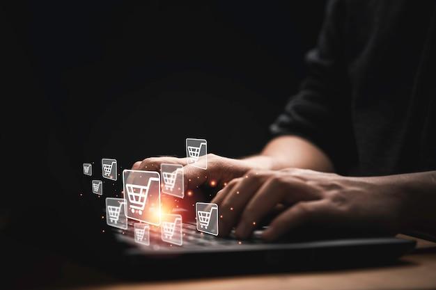 온라인 쇼핑 개념을 위한 입력 주문을 위해 쇼핑 카트 아이콘이 있는 컴퓨터 노트북을 사용하는 사업가입니다.