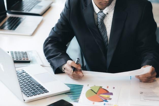 Бизнесмен, используя компьютер для анализа инвестиций.