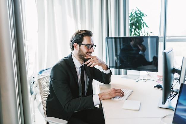 Бизнесмен, используя настольный компьютер, сидя в своем офисе. одна рука на подбородке, а другая на клавиатуре.