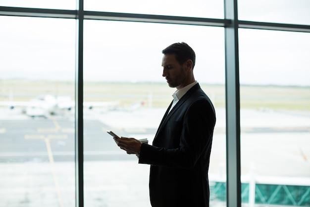 Бизнесмен с помощью цифрового планшета в зоне ожидания
