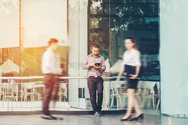 Businessman using a digital tablet office outdoors and blurred people walking