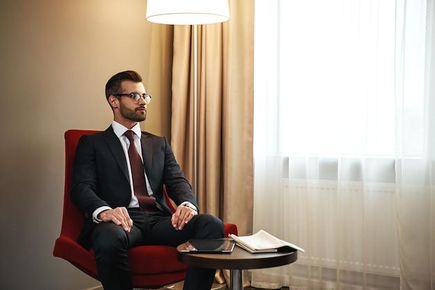 Бизнесмен с помощью цифрового планшета на красном стуле в гостиничном номере