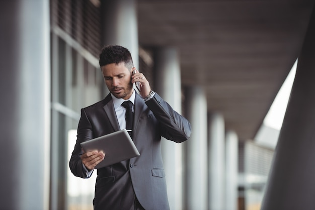 Businessman using digital tablet while talking on mobile phone