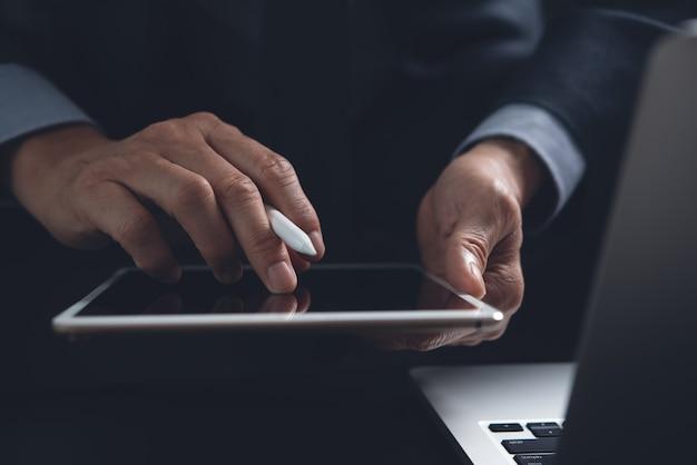 Бизнесмен с помощью цифрового планшета, работающего на портативном компьютере на офисном столе