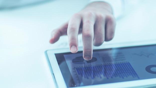 책상에서 재무 일정으로 작업하는 디지털 태블릿을 사용하는 사업가