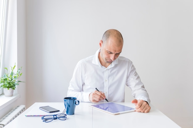 Businessman using graphic digital tablet at workplace
