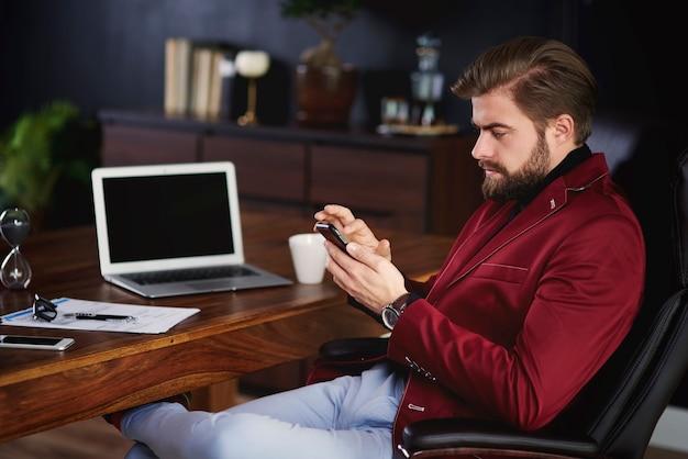 ホームオフィスで彼の携帯電話を使用してビジネスマン