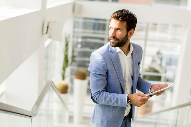 Businessman using his digital tablet at the office