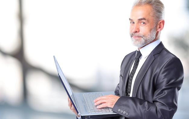 ビジネスマンはオフィスで彼のラップトップを使用しています