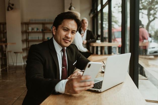 カフェで彼の携帯電話を使用してビジネスマン
