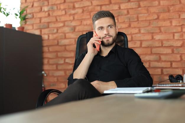 Бизнесмен, используя свой мобильный телефон в офисе.