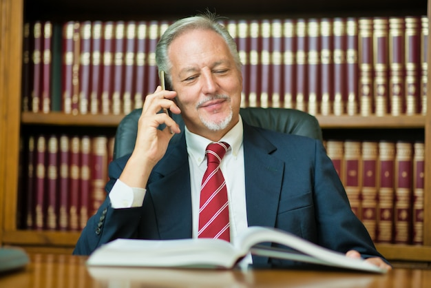 Businessman using his mobile phone while reading a book
