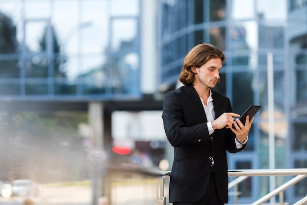 Businessman using his tablet outdoors