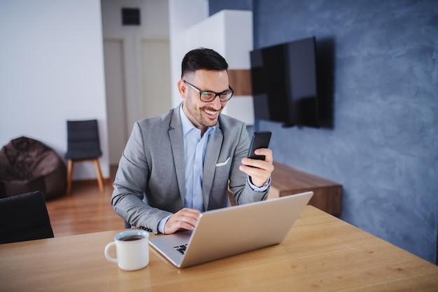 自宅でノートパソコンと携帯電話を使用しての実業家。
