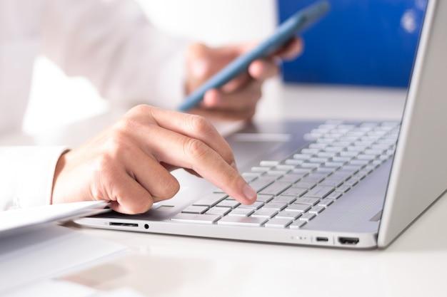 노트북과 집에서 컴퓨터에서 작동하는 스마트 폰을 사용하는 사업가. 사업가 가정에서 또는 온라인 학습 개념에서 작동합니다.