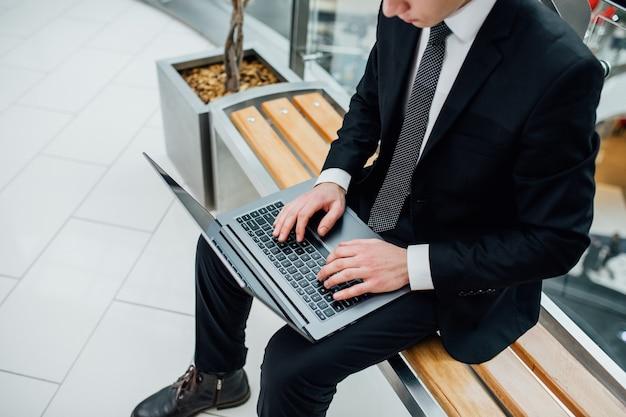 ラップトップコンピューターを使用してビジネスマン。ノートパソコンのキーボードで入力する男性の手のクローズアップ。