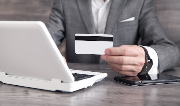 Businessman using laptop computer and holding credit card.