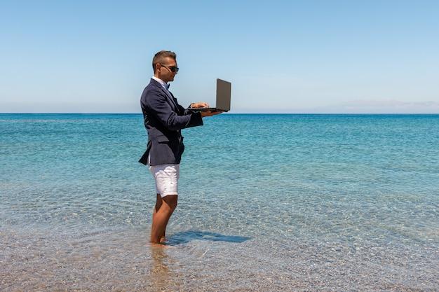 熱帯のビーチでラップトップコンピューターを使用して実業家