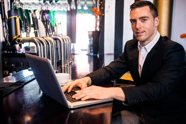 Businessman using laptop at the counter in a bar