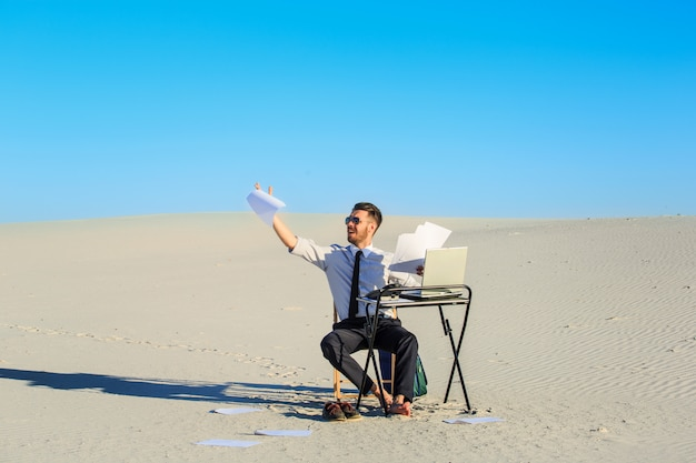Businessman using laptop in a desert