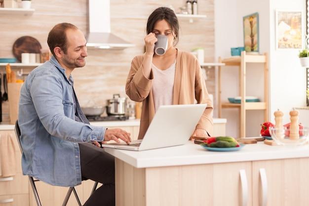 부엌과 wi-fi에서 노트북을 사용하는 사업가가 커피 한 잔을 마시고 있습니다. 현대적인 wi-fi 무선 인터넷 기술을 사용하여 집에서 사랑하는 부부의 행복한 사랑의 쾌활한 낭만적인