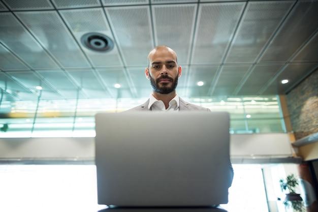 Бизнесмен, используя ноутбук в зоне ожидания
