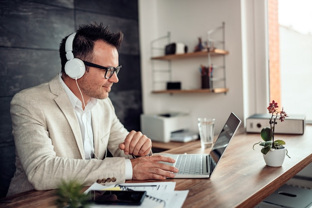 Businessman using laptop and listening music on headphones